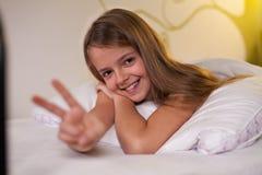 Chica joven que muestra la muestra que miente en cama, profundidad baja de la victoria Fotografía de archivo