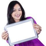 Chica joven que muestra la pantalla vacía de la tableta Foto de archivo