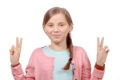 Chica joven que muestra sus manos haciendo gesto de la victoria Imágenes de archivo libres de regalías