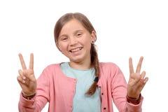 Chica joven que muestra sus manos haciendo la victoria Fotos de archivo