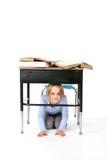 Chica joven que oculta bajo un escritorio de la escuela Imagen de archivo libre de regalías