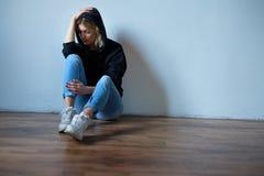 Chica joven que oculta su cara debajo de la sudadera con capucha aislada en b Imagenes de archivo