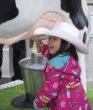 Chica joven que ordeña una vaca Fotos de archivo libres de regalías