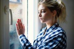 Chica joven que parece hacia fuera la ventana y que siente triste Foto de archivo