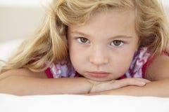 Chica joven que parece triste en cama en dormitorio Fotos de archivo libres de regalías