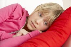 Chica joven que parece triste en el sofá Imágenes de archivo libres de regalías