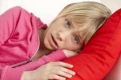 Chica joven que parece triste en el sofá Fotografía de archivo