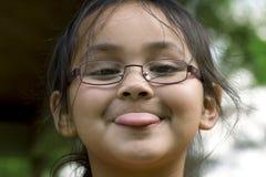 Chica joven que pega hacia fuera su tounge Imagen de archivo
