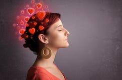 Chica joven que piensa en amor con los corazones rojos Foto de archivo