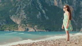 Chica joven que piensa en la playa del mar contra las montañas Cabrito en agua almacen de video