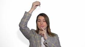 Chica joven que piensa y que tiene una idea que señala la mano encima de aislado sobre el fondo blanco metrajes