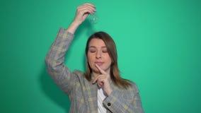 Chica joven que piensa y que tiene una idea que señala la mano encima de aislado sobre fondo verde metrajes