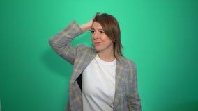 Chica joven que piensa y que tiene una idea que señala la mano encima de aislado sobre fondo verde almacen de video