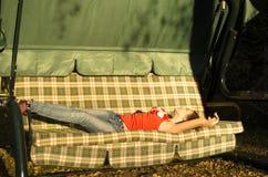 Chica joven que pone en el daybed Imagen de archivo
