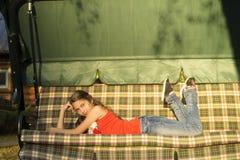 Chica joven que pone en el daybed Fotos de archivo