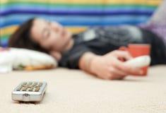 Chica joven que pone en el suelo que mira la televisión Foto de archivo libre de regalías