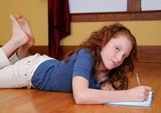 Chica joven que pone en la escritura del suelo Foto de archivo libre de regalías