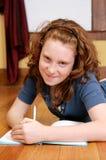 Chica joven que pone en la escritura del suelo Fotos de archivo libres de regalías
