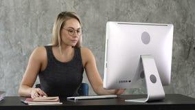 Chica joven que pone en los vidrios y comienzo que trabaja en el ordenador que se sienta en la tabla metrajes