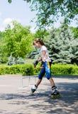 Chica joven que practica en un parque del patín Fotografía de archivo