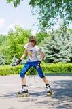 Chica joven que practica en un parque del patín Foto de archivo