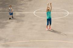 Chica joven que practica en una cancha de básquet Fotos de archivo