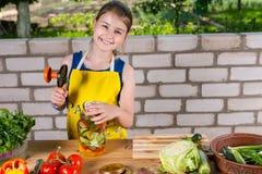 Chica joven que prepara las verduras frescas para conservar Imágenes de archivo libres de regalías