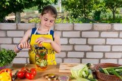 Chica joven que prepara las verduras frescas para conservar Fotografía de archivo