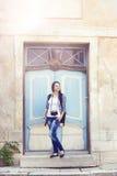 Chica joven que presenta al lado de una puerta del vintage Fotos de archivo
