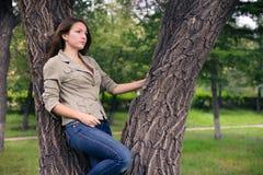 Chica joven que presenta cerca del árbol Imagen de archivo