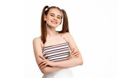 Chica joven que presenta con los brazos cruzados aislados en el fondo blanco Fotografía de archivo