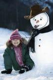 Chica joven que presenta con su muñeco de nieve Imagen de archivo