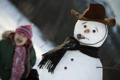 Chica joven que presenta con su muñeco de nieve Imagen de archivo libre de regalías