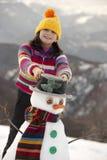 Chica joven que presenta con su muñeco de nieve fotografía de archivo
