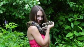 Chica joven que presenta con una serpiente alrededor de su cuello en la naturaleza almacen de video