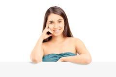 Chica joven que presenta detrás de un panel en blanco Imagenes de archivo