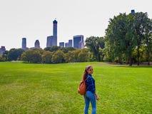 Chica joven que presenta en el prado en Central Park, NY, Nueva York de las ovejas imagenes de archivo