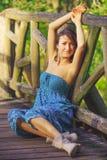 Chica joven que presenta en el puente de madera Imagen de archivo