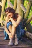 Chica joven que presenta en el puente de madera Imagenes de archivo