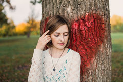 Chica joven que presenta en parque cerca del árbol con el corazón rojo grande pintado Fotografía de archivo libre de regalías