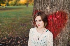 Chica joven que presenta en parque cerca del árbol con el corazón rojo grande pintado Imagenes de archivo