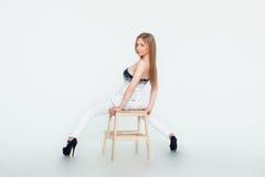 Chica joven que presenta en un fondo del blanco del estudio Imagenes de archivo