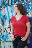 Chica joven que presenta en una pared de la pintada con la camiseta roja Fotografía de archivo libre de regalías