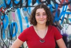 Chica joven que presenta en una pared de la pintada con la camiseta roja Fotografía de archivo