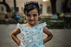 Chica joven que presenta en vestido tradicional en la ciudad emparedada histórica del camino de seda foto de archivo