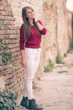 Chica joven que presenta la pared de ladrillo retra Imagen de archivo libre de regalías