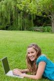 Chica joven que ríe mientras que pulsa en su computadora portátil Imagen de archivo