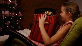 Chica joven que recibe el gatito en una caja de regalo grande para la Navidad almacen de video