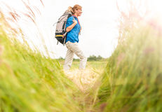 Chica joven que recorre en prado con el morral encendido. Foto de archivo