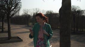 Chica joven que saca el teléfono del bolsillo y de los textos un mensaje que lleva la chaqueta verde de la moda y la falda color almacen de metraje de vídeo